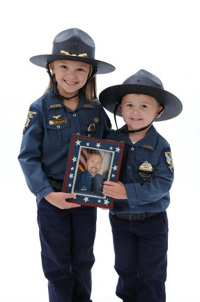 Callie and Wyatt Christian hold a picture of their father, Buddy Christian